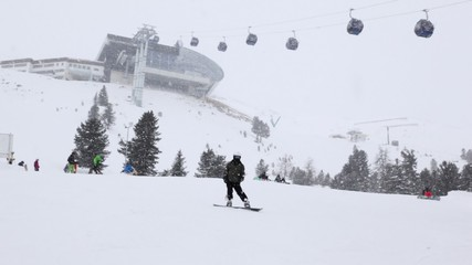 Skiers and snowboarders go for drive near ropeway station