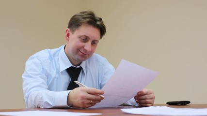Man reading document and signs it in office real estate agent