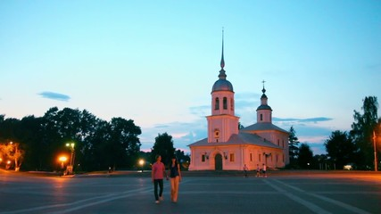 Couple approach by Kremlin square in Vologda, Russia