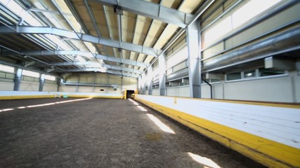 Empty indoor horse riding hangar with sandy covering