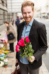 Businessman holding flowers and smiling