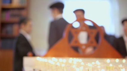jewish boys near funeral candles and wooden merkaba in synagogue