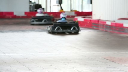 Two young boys having a race in carting on cating course