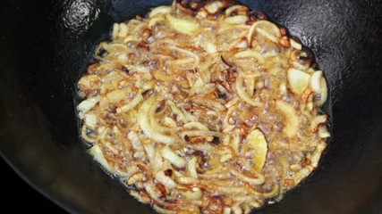 Lot of broiled onion boils in hot oil at pot closeup