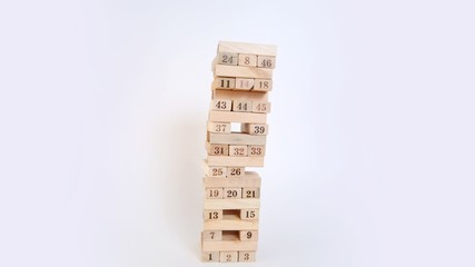 Wooden cubes with numbers are built in high tower on white background, time lapse