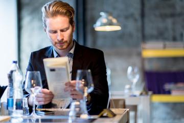 Businessman holding the menu in a restaurant