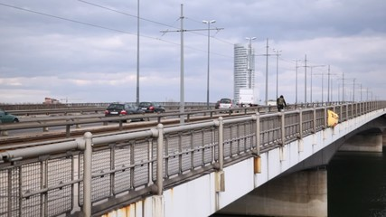 Cyclist and cars follow on the bridge at cloudy day.