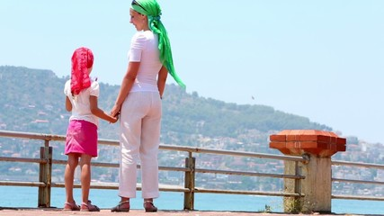Mother and little daughter stand on bunder looking at bay