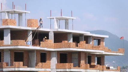 Workers erect balconies from brick in new building at top floor in afternoon, time laps