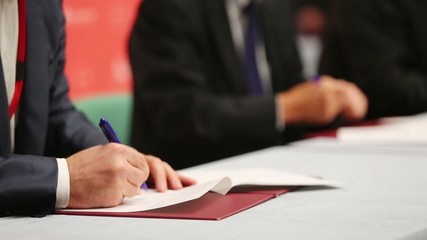 Hands of men at table sign documents at business meeting