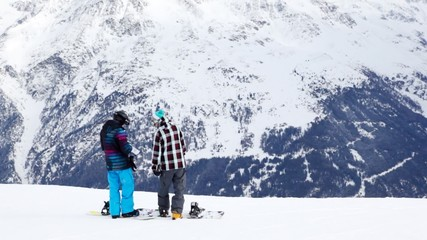 snowboarders stand and discuss further route on mountain slope