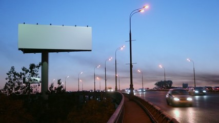 Empty advertising pillar on sidelines of highway with traffic at evening