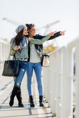 Two young women looking over a dock fence and pointing