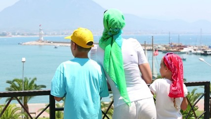 Mother and two children look at bay during promenade, rear view