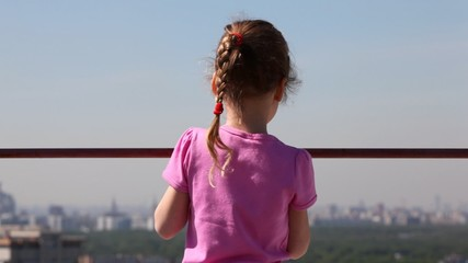 little girl stands back against dim city landscape in afternoon