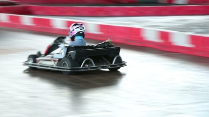 Young boy having fun in kart making a lap on course