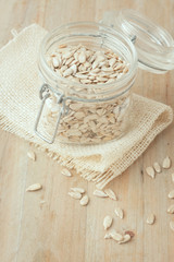hulled sunflower seeds in glass jar on wooden rustic background