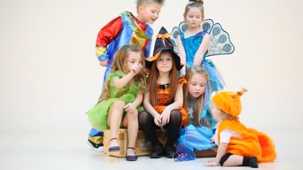 Six little children in costumes talking isolated on white