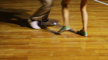 Male and female legs dance boogie-woogie on wooden floor