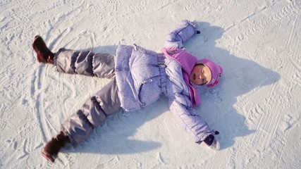 Little girl lies on snow and moves her arms and legs