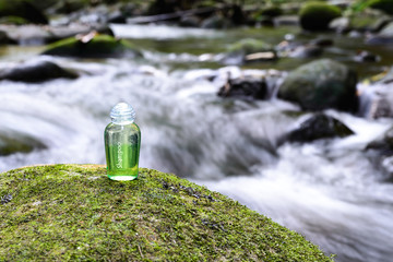 Spa shampoo on moss stone with waterfall background.