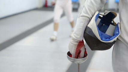 Fencer hold rapier and helmet, closeup view in sport club during training
