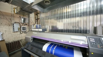 Plotter in printing house prints blue image on a large paper