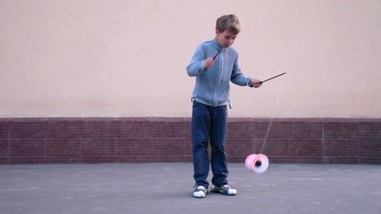 Boy uses two sticks with rope between for manipulate circling toy