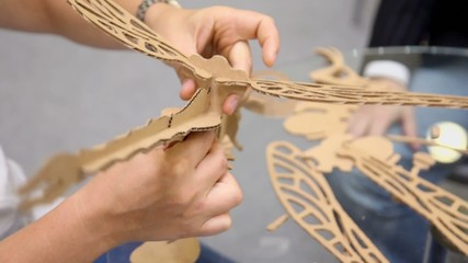 Hands makes dragonfly model from cardboard material, closeup
