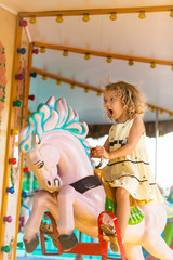 A young girl enjoying a ride on the merry-go-round.