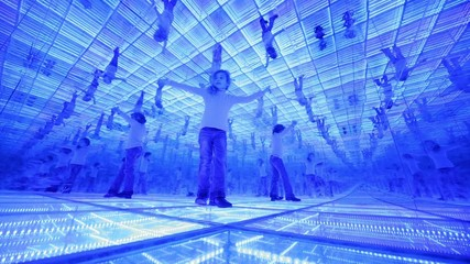 Little girl have fun in a mirrored room with blue lights