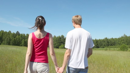 man and woman go across field to wood holding hands
