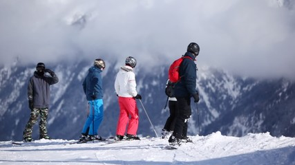 Skiers prepare for start on ski route against mountain gorge