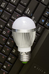 Close up Led Bulb at the keyboard background. Vertical.