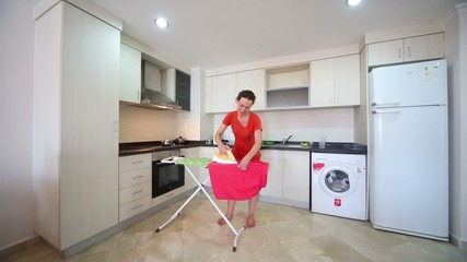 Beautiful barefoot housewife ironing laundry in kitchen