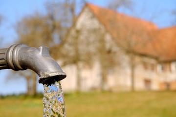 an einem Brunnen im Schwarzwald mit Bauernhof