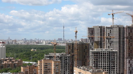 complex of multystoried buildings under construction against city landscape, wood and television tower