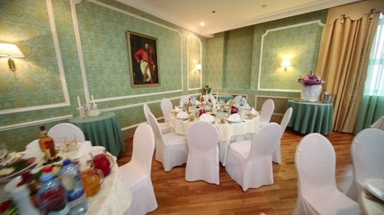 Review tables in restaurant decorated for wedding celebration