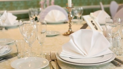 Close-up review decorated wedding table with glasses and cutlery