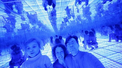 Family of three have fun in a mirrored room with blue lights