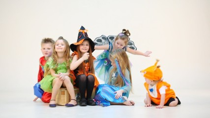 Six children in costumes siting isolated on white