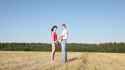 girl stands having placed hands in field, guy stands nearby
