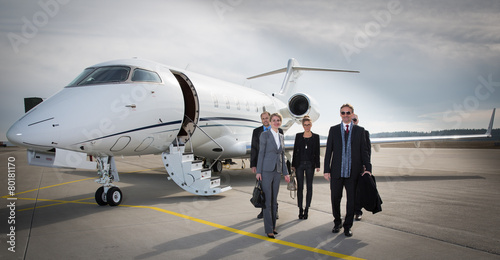 Leinwanddruck Bild executive business team leaving corporate jet