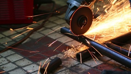 Male hand cuts off pieces of water pipe with angle grinder.