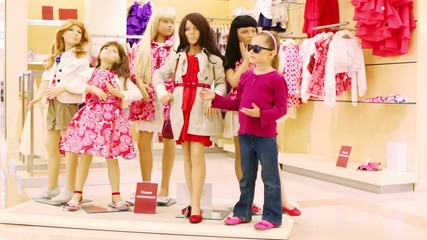 Little girl imitates mannequins in store of childrens clothes