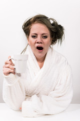 tired woman holding coffee cup in her hand