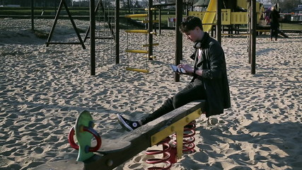 Student smiling to the camera and sitting on seesaw