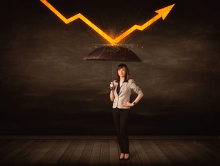 Businesswoman standing with umbrella keeping orange arrow