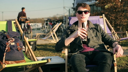 Student drinking beer and cheers to the camera in outdoor bar