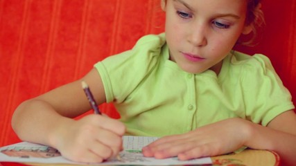 Little girl paints on paper by pencil against red wall
